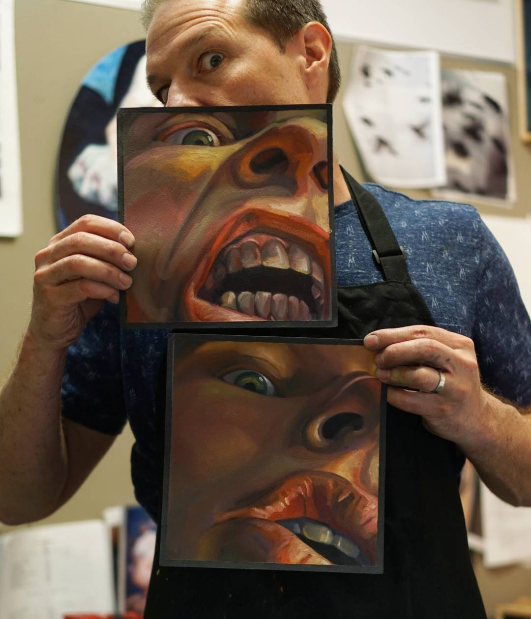 Instagram photo of Scott Hutchison in his studio posing in front of Face #1 and Face #2